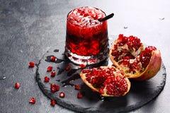 Odświeżający egzotyczny napój i rżnięty garnet na szarym tle Czerwony bezalkoholowy sok z lodem Zimno słodkogórzki Zdjęcie Stock
