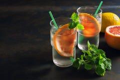 Odświeżający koktajl z grapefruitowym i nowym Szkło zaparowywał z zimną wodą i plasterkiem grapefruitowy Ciemny tło, backlight Obrazy Stock