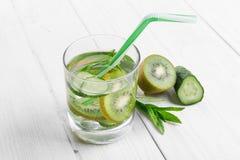 Odświeżający napój dla detoxification, woda mineralna w zielonym kiwi, mennicie i ogórku na białym stole szklanych, świeżych, fotografia royalty free