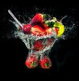 Odświeżający truskawkowy deser w imaginacyjnym pucharze z wody bryzga na czarnym tle zdjęcia royalty free