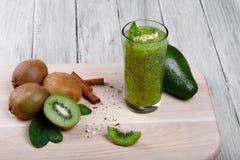 Odświeżający zielony smoothie od kiwi owoc z ziarnami, avocado, orzechami włoskimi, cynamonem i mennicą na świetle drewnianym cze Obrazy Stock