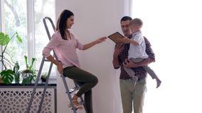 Odświeżanie praca zespołowa mieszkanie, szczęśliwa rodzina z dzieckiem robi naprawom w mieszkaniu i zrozumienie obraz, używać ste zbiory