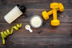 Odżywianie dla mięśnia przyrosta Miarka proteinowy pobliski potrząsacz, dumbbell, pomiarowa taśma na ciemnego drewnianego tła odg obraz stock