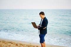 Od biura morze Młodego człowieka biznesmena bieg w morze z laptopem Fotografia Stock