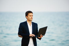 Od biura morze Młodego człowieka biznesmena bieg w morze z laptopem Obrazy Royalty Free