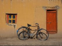 An old black vintage bicycle with large wheels stands near the yellow wall between the window with a wooden frame and a wooden bro. Od black vintage bicycle with Stock Photo