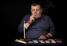 Od man smoking cigar before cartomancy Stock Image