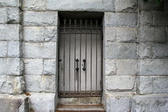 Od stone crypt with locked doors behind cast iron gate Stock Photography