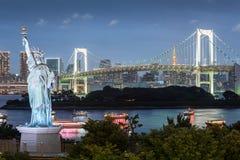 Odaiba-Freiheitsstatue mit Regenbogenbrücke und Tokyo ragen am Abend hoch lizenzfreie stockfotos