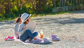 ODAWARA, JAPAN - NOVEMBER, 11, 2017: Two girls in the park draw. With pencils. Copy space for text stock photos