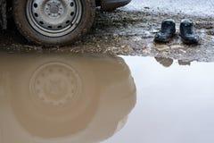 Odbicia koła samochód w błotnistej kałuży i mężczyzna butach Fotografia Royalty Free