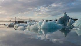 Odbicie kostki lodu i wiszący most przy Jokulsarlon lodowa laguną Fotografia Royalty Free