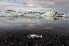 Odbicie kostki lodu z czarnym żwirem i małym kostki lodu przedpolem przy Jokulsarlon lodowa laguną Obraz Royalty Free