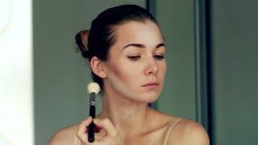 Odbicie młoda piękna dziewczyna stosuje jej sztuka makijaż, patrzeje w lustrze zbiory