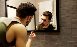 Odbicie młody człowiek patrzeje na jego twarzy w łazienki lustrze Obraz Royalty Free