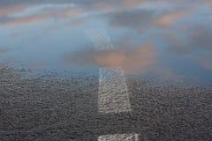 Odbicie niebo w mokrej kałuży i asfalcie po tym jak deszcz w położenia słońcu, Drogowy ocechowanie iść w wodę Zamknięty u Zdjęcia Royalty Free