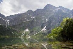 Odbicie Tatrzańscy halni szczyty w oku Denny jezioro Oko Denny jezioro w Tatrzańskich górach, Polska Polski Tatrzański Obraz Stock