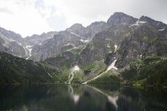 Odbicie Tatrzańscy halni szczyty w oku Denny jezioro Oko Denny jezioro w Tatrzańskich górach, Polska Polski Tatrzański Fotografia Royalty Free