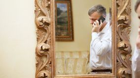 Odbicie w lustrze przystojny mężczyzna, Młody biznesmen w białej koszula, trzyma smartphone, telefon komórkowy zbiory wideo