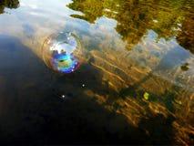 Odbicie w mydlanym bąblu unosi się w dół rzekę Zdjęcie Royalty Free