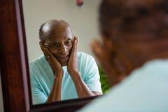 Odbicie zaniepokojony starszy mężczyzna na lustrze zdjęcie royalty free