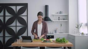 Odchudzający jedzenie, szczęśliwa dziewczyna ciie zielenie dla zdrowej żywienioniowej sałatki dla lunchu na kuchennym stole używa zbiory