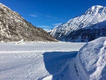 Odciski stopy dosięga przez zamarzniętego jezioro z górami Obrazy Stock