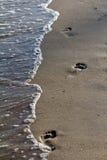 Odciski stopy na piaskowatej plaży przy ciepłym wieczór zaświecają Zdjęcia Royalty Free