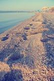 Odciski stopy na piaskowatej plaży w lecie; zatarty, retro styl, Obrazy Royalty Free