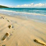 Odciski stopy na piasku przy piękną plażą Zdjęcie Royalty Free