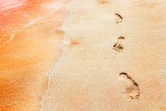 Odciski stopy na stubarwnym różowym piasku na opustoszałej czerwieni wyrzucać na brzeg tropikalny tło piasek samochodowej miasta  Zdjęcia Royalty Free