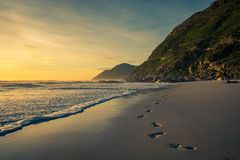 Odciski stopy w piasku przy zmierzchem zdjęcie stock