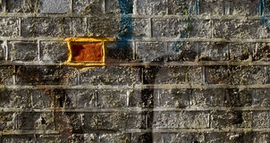 Odd brick. An odd brick in a wall of graffiti depicting difference Royalty Free Stock Photos