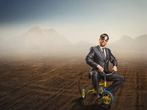 Odd businessman riding a small bicycle Royalty Free Stock Photos