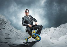 Odd businessman riding a small bicycle Royalty Free Stock Images