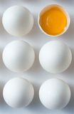 Odd Egg Out 2. Six eggs on a white background.  Five eggs have undisturbed white shells; the sixth is halved with the yolk visible inside.  Shot from above Royalty Free Stock Image