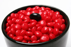 Odd one. Red jelly beans in bowl with a black jelly bean royalty free stock photos