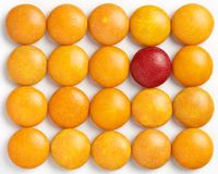 The odd one in the group on white. Colorful coated chocolates on a white background with one red odd one Stock Images