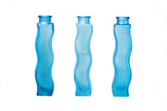 Odd one out. 3 wavy blue glass bottles. The 3rd bottle is facing in the opposite direction to the other two. Isolated on a white background Stock Photo