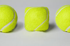 Odd one Out. Close up of Three tennise balls one of which is square Stock Photography