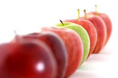 Odd One Out. A green apple is the odd one out in a line of red Royalty Free Stock Photos