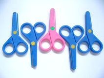 Odd one out (pink). Odd pink scissors among blue scissors Royalty Free Stock Photography