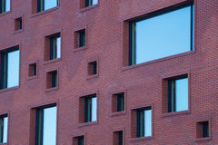 Odd sized windows on brick wall of modern building Royalty Free Stock Images