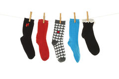 Odd Socks. Whose mates have been lost, hanging on a clothesline.  Shot on white background Stock Images