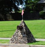 Odd Stone Mailbox topped with U.S Flag Stock Photo