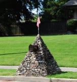 Odd Stone Mailbox överträffade med U S-flagga Arkivfoto