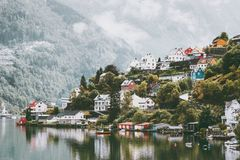 Odda city houses in Norway Landscape. Foggy mountains and water reflection Stock Photo