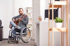 Oddany niepełnosprawny mężczyzna bawić się instrument muzycznego zdjęcia stock