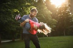 Oddany ojciec wiruje jego córki w okręgach fotografia stock