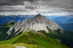 Oddly shaped Crode dei Longerin peak and Friuli Dolomites. Oddly shaped sharp Crode dei Longerin peak, green hills in Carnic Alps with rocky Dolomiti Friulane Royalty Free Stock Image